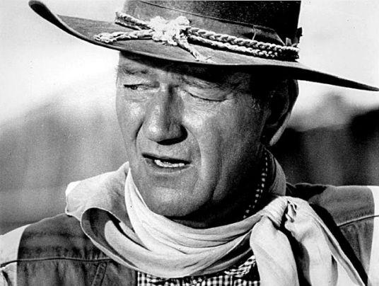Black and white picture of John Wayne, dressed as a cow boy