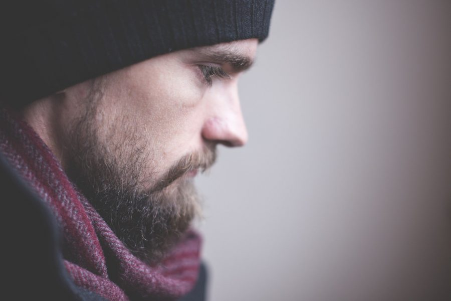 a side profile of a bearded man with a wooly hat on and a red scarf who looks sad
